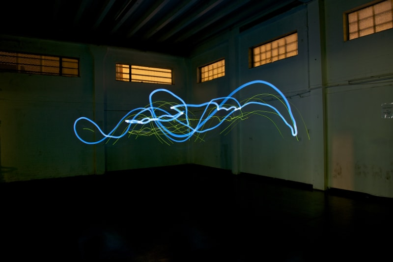 A photo taken in a dark warehouse from below. There's a single blue line of light drawn erratically in the center.