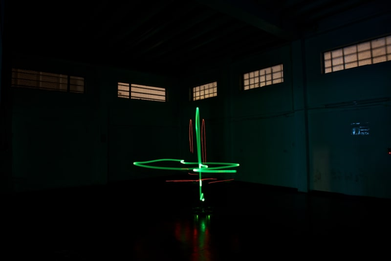 A photo taken in a dark warehouse from below. A green light is in the center in a cross shape.