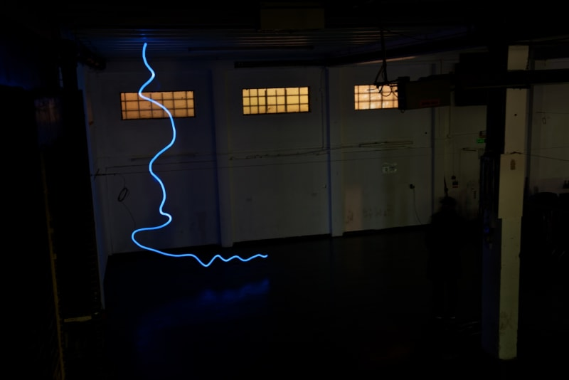 A photo taken in a dark warehouse from above, looking down. There's a single blue line of light snaking from the floor to the ceiling.
