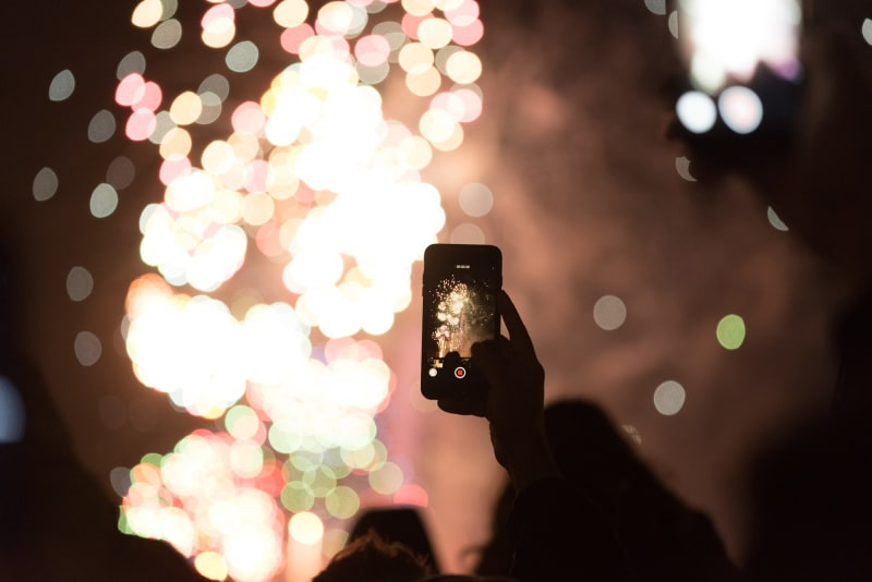 A phone is held taking a photo of fireworks in the distance.