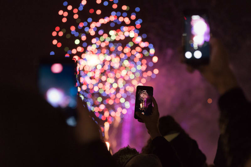 Three phones are held in the air taking photos of fireworks in the distance.