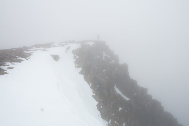 A photo of a rocky cliff partially covered in snow. There's strong fog everywhere so the background and bottom of the cliff can't be seen. There's a shadow of a person at the tip of the cliff.