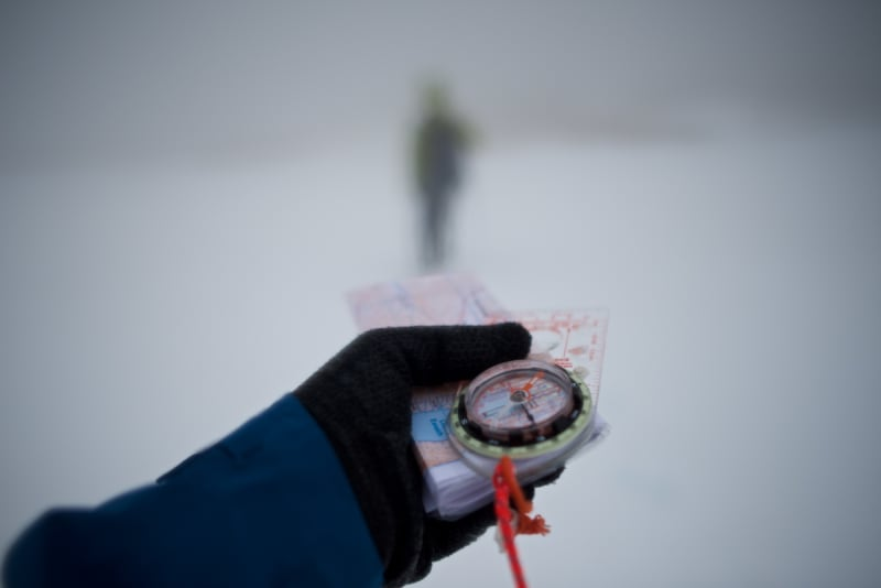 A gloved hand holds a compass and map in front of the camera as a blurred figure walks ahead in the distance surrounded by snow and fog.