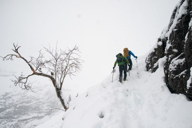 Two hikers climb a somewhat steep snowy hillside. It's overcast with flurries of snow around.
