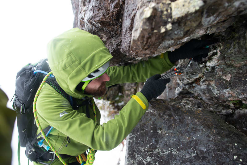 Ed stoops low to place a piece of climbing gear in a rockface.
