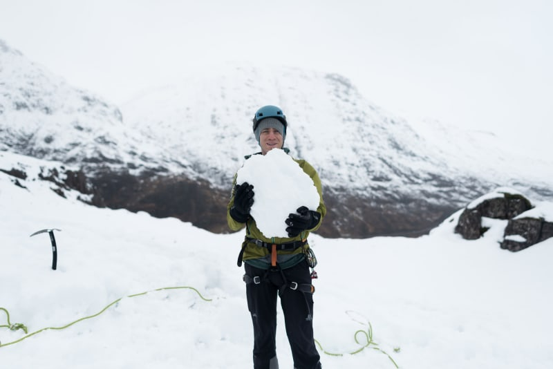 Chris holds a large boulder of snow as he faces the camera.