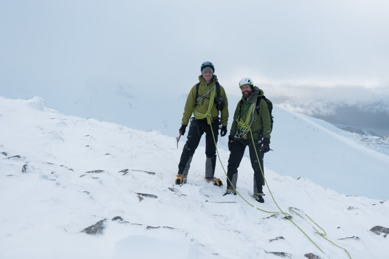 Ed and Chris pose together facing the camera on the edge of Aonach Mòr. Both are wearing green jackets and are tied together with a green climbing rope.