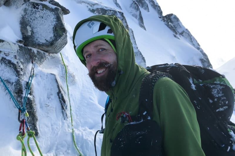 Ed wearing a green softshell jacket with hood over his helmet on the side of a snowy mountain.