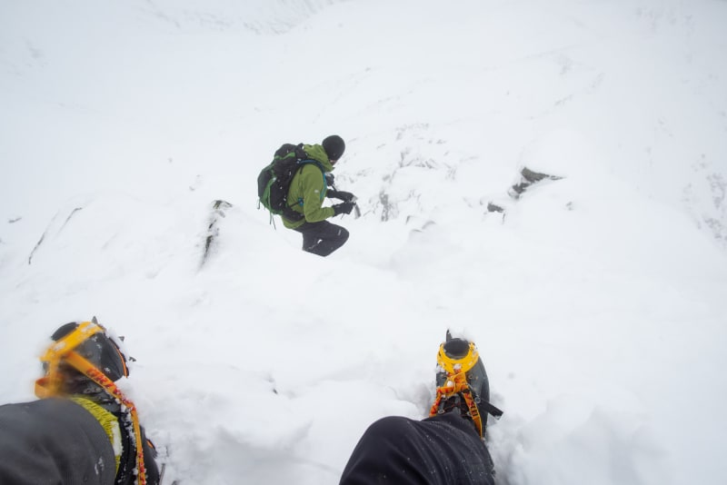 Two boots with crampons on are in the foreground descending a steep snowy mountain. Ed can be seen a few meters ahead.