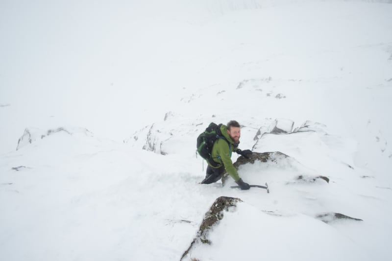 Ed looks back to the camera as he descends a steep snowy ridge.