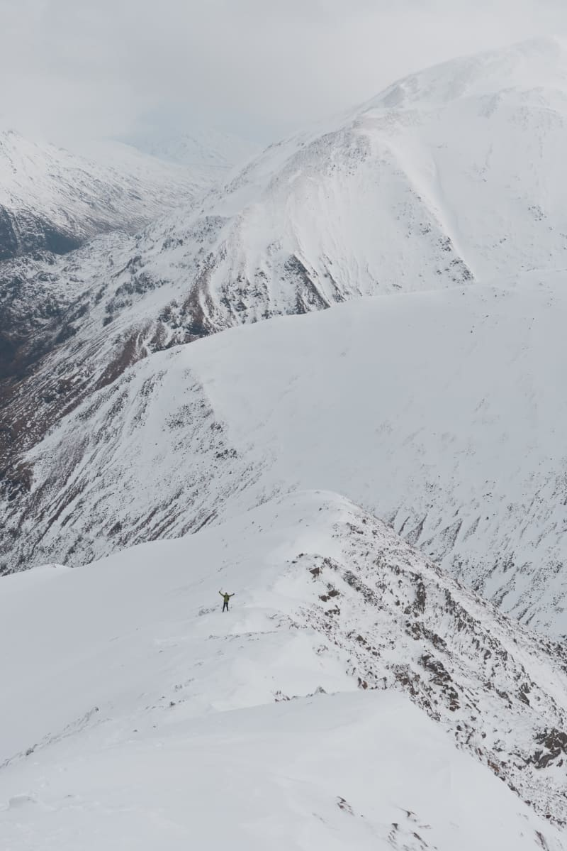 A long photo looking down a snowy mountain to the valley. The small figure of Chris is visible in the distance with both hands in the air waving to the camera.