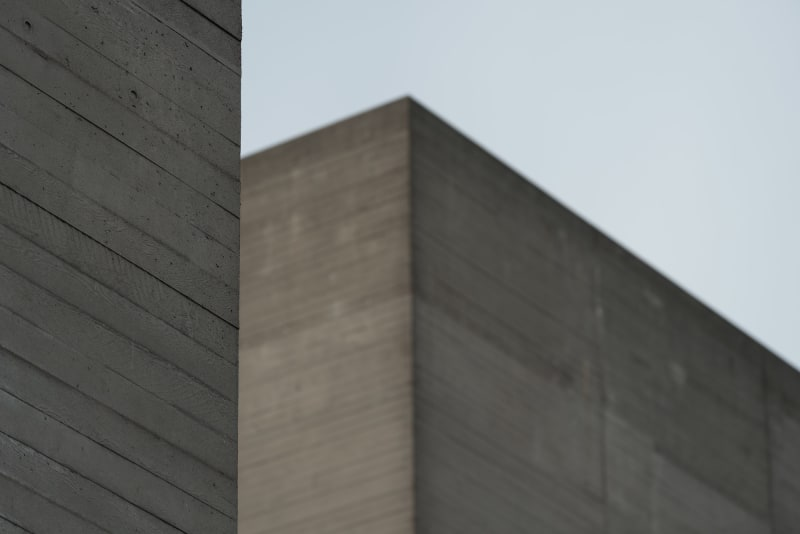 A close detail of a section of the National Theatre's roof. In the foreground is the edge of a corner of concrete with wood effect. In the background another building roof can be seen slightly blurred.