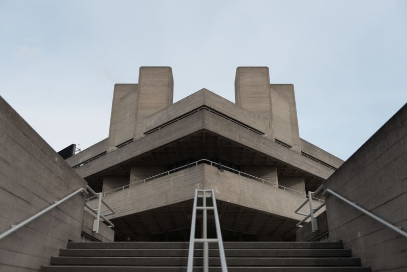 Looking up at one of the entrances to the National Theatre. The photo is symmetrical - the corner leads to a stairwell at 45º, and the camera is at the bottom of the stairs.
