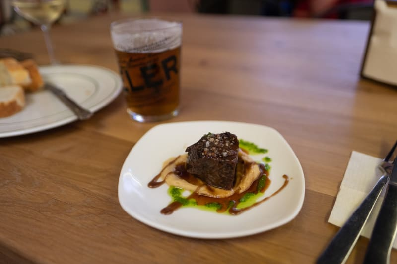 A small piece of beef sits on a plate green vinaigrette and a glass of beer in the background.
