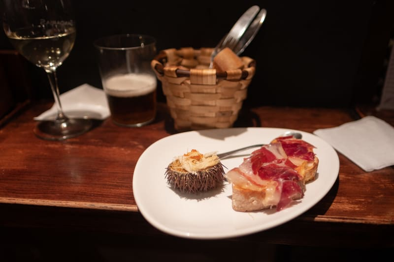 A plate of pintxos on a wooden bench next to a basket of bread, a glass of beer, and a glass of white wine. One pinxto is a slice of baguette with ham. The other is half of a sea urchin.
