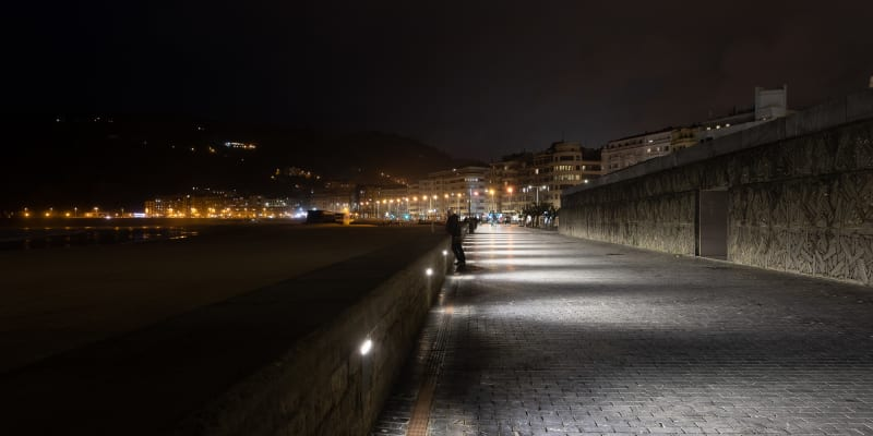 At night time, looking down the beach promenade to the city. There's a mix of yellow sodium lamps with more modern white leds.