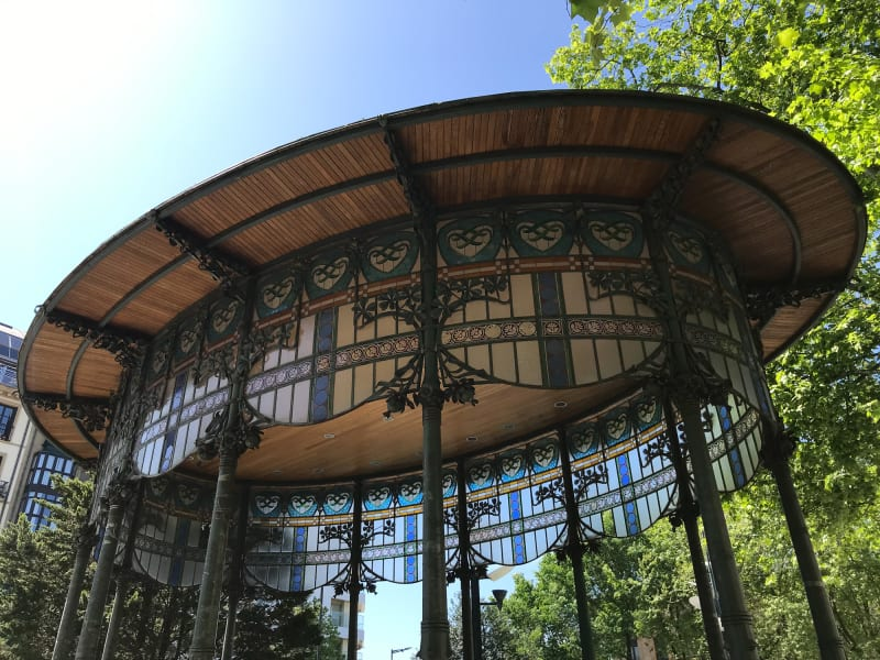 Looking up at an ornate bandstand roof. The bandstand is oval in shape and the upper walls have stained glass.