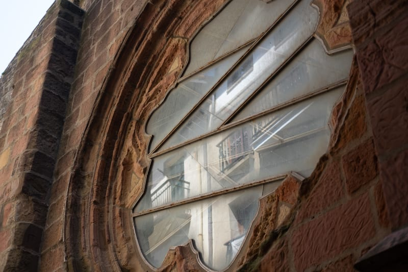 Looking up at the exterior of a church window. The surround is made from brown bricks, and you can see the neighbouring building reflected in the window glass.