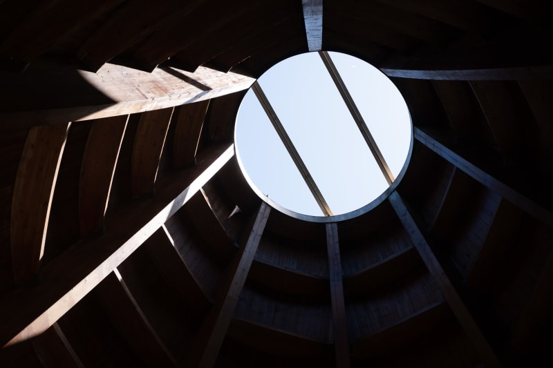 Looking up to a circular opening in a wooden roof.