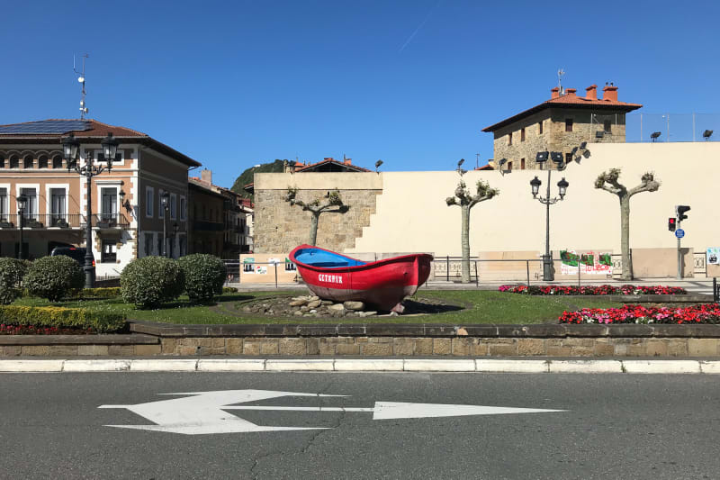 Looking across to the other side of a street in Getaria. In the central divider there is a red rowing boat.