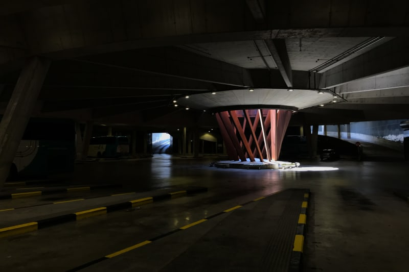 Inside the San Sebastián bus station. The loading bay is large and dark, with a circular sculpture in the middle, letting light in from above.