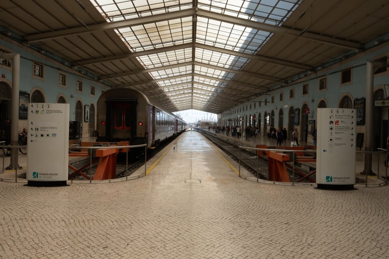 Looking directly down the central platform in a train station. On the left a train is waiting. The station is small and with a low roof.