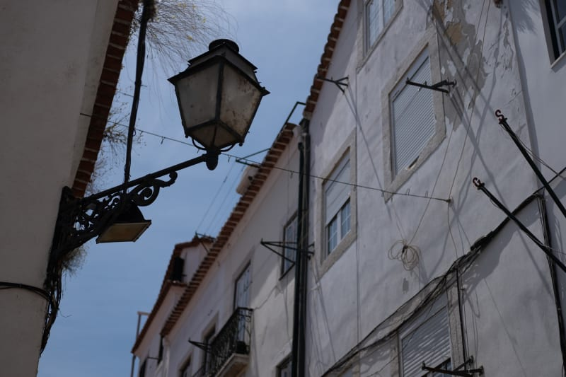 Looking up at a streetlamp in a narrow street. It's daylight, so the streetlamp isn't on.