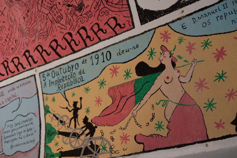 A painting on a wall in the form of a comic strip. The main visible text starts '5 Outubro de 1910'.