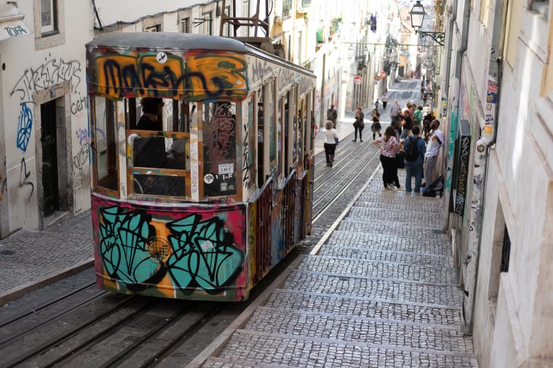 A funicular car descending a steep street in bright sunlight.