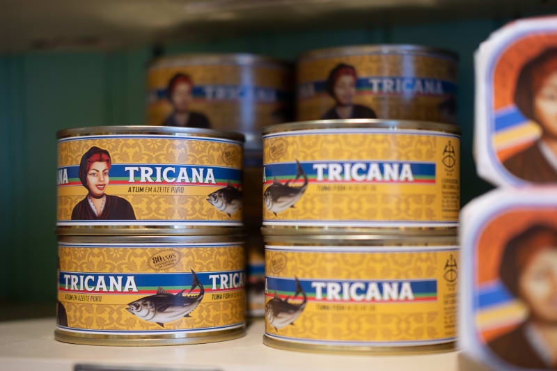 A macro photo of several cans of tuna stacked on a shelf. The cans have a vintage look and are labeled 'Tricana'.