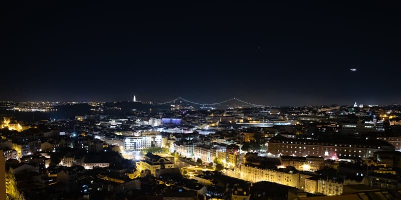A panorama of Lisbon at night. The streets are filled with yellow and white lights and a suspension bridge can be seen in the distance.