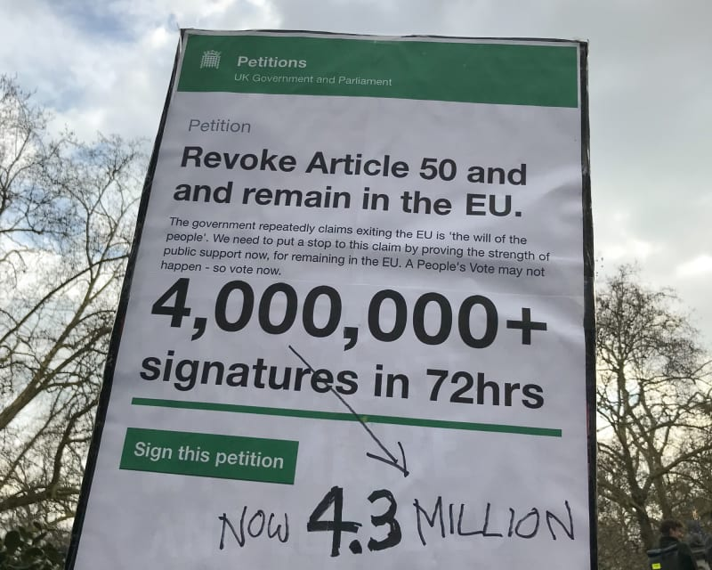 A large protest sign high in the air. The sign shows the Article 50 petition on petition.parliament.uk and in large letters shows that it had more than 4.3 million signatures.