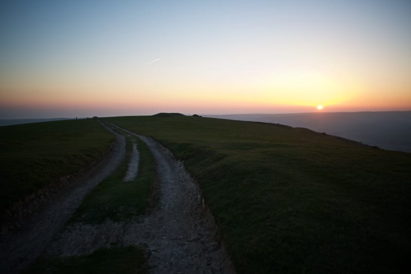 A chalky path recedes in to the distance on a hillside. The sun is just setting on the horizon.