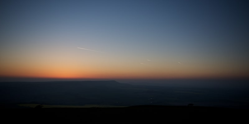 Twilight over the South Downs. The sky is clear with yellow and orange hues on the horizon.