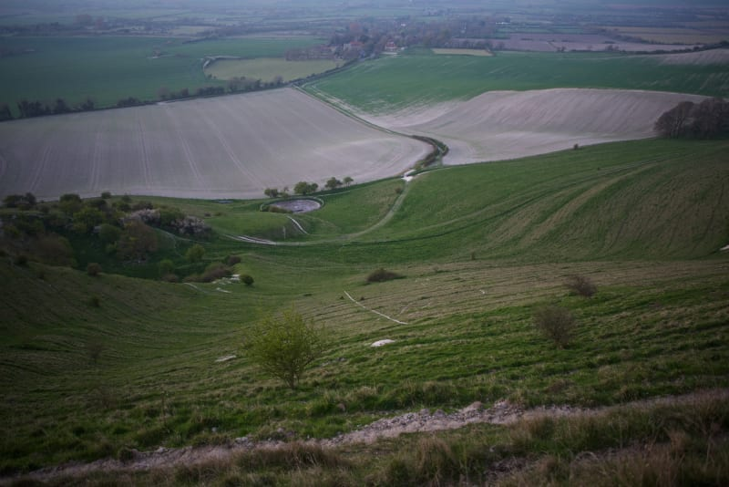 Looking down a grassy hill with a farm in the distance. A faint chalky line can be seen on the ground - part of the Long Man of Wilmington.