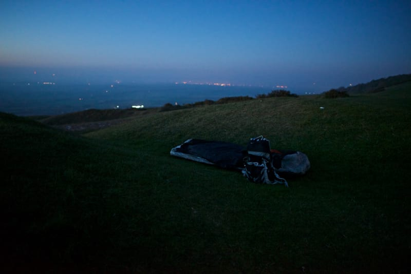 A bivvy bag and rucksack sit in a hollow depression in the grass in the last of the evening light. The sky is dark blue and calm.