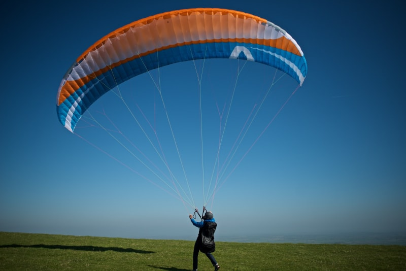 A paraglider stands on the ground with a large sail inflated overhead.