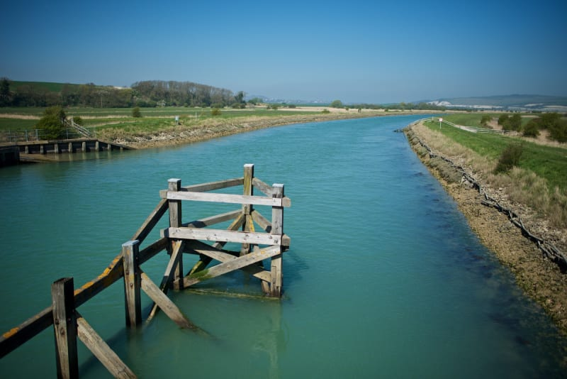 Looking down a greenish-blue river, with rotting wooden posts in the foreground.