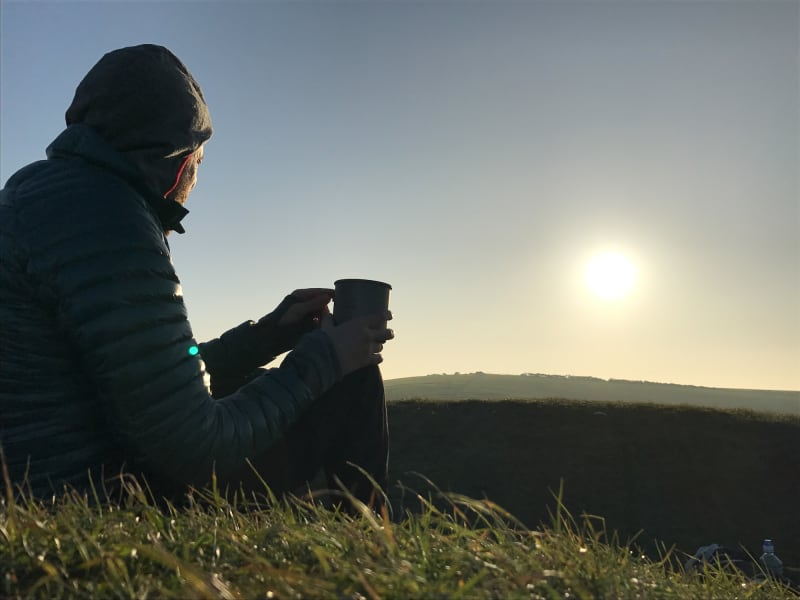 A photo at sunrise of Ed Horsford sitting on a grassy hill with a cup in hand looking over a hill.
