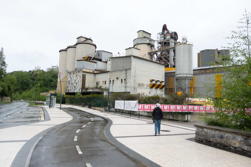 Lynn stands in front of the Rezola cement factory. There's a winding cycle path in front of her.