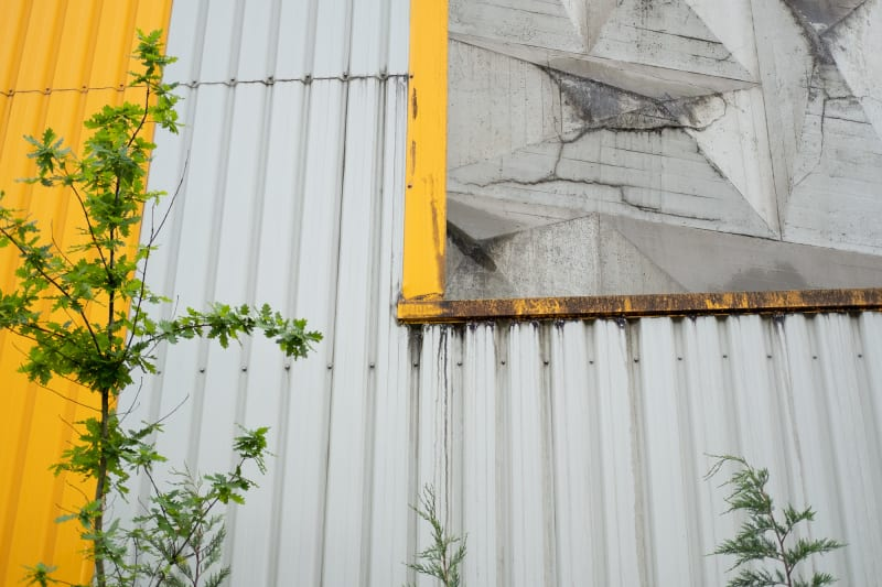 A close shot of the wall of the Rezola cement factory. The wall is made of grey corrugated steel with yellow trim.