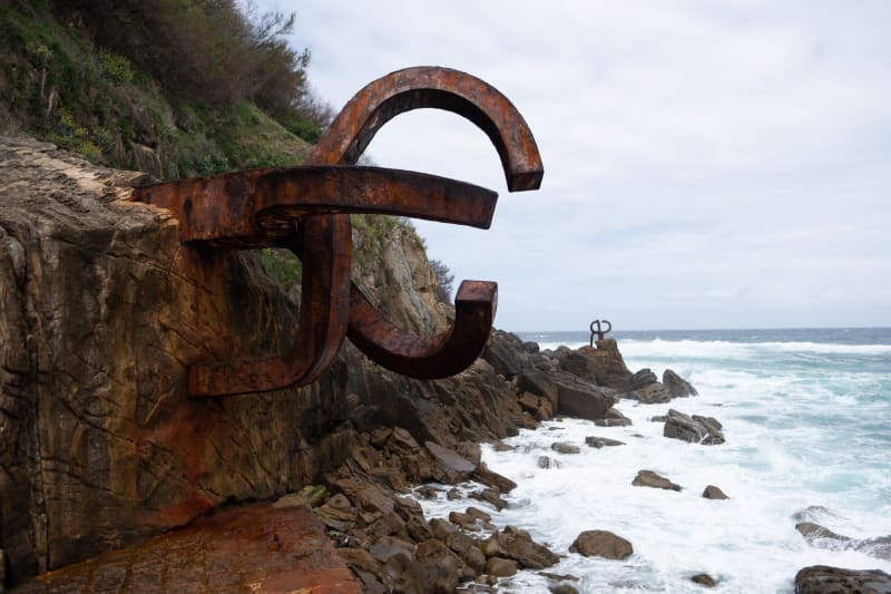 A photo of two parts of a large iron sculpture by artist Eduardo Chillida. The sculptures sit on the coastline with the sea to the right. One piece dominates in the foreground, with another just visible in the background.