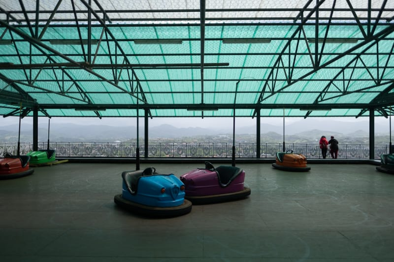 Bumper cars sit unused at the top of a mountain. In the background the city of San Sebastián can be seen below.