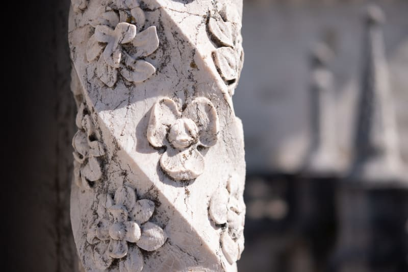 A close detail shot of an aged carved marble pillar in the Torre de Belém. The column has a spiral shape with fine flowers carved at regular intervals.