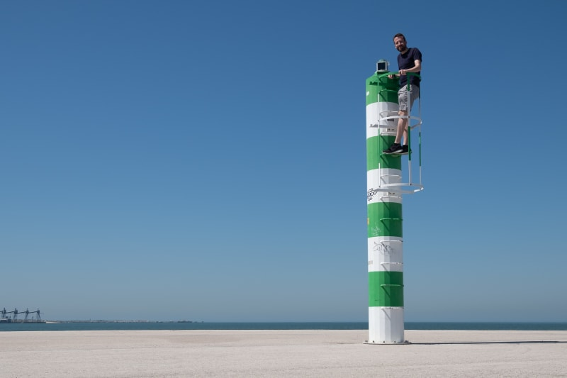 A photo of a small warning beacon on a pier. The beacon is painted in white and green stripes. Ed Horsford is stood on a ladder near the top, looking at the camera.