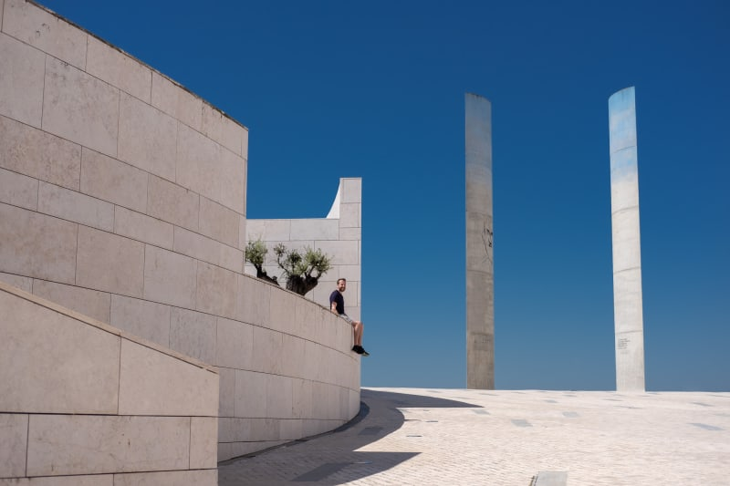 A photo taken in the courtyard of the Champalimaud Foundation. There's a raised platform on the left, with Ed Horsford sat looking at the camera. On the right are two tall concrete towers set against a very deep blue sky.