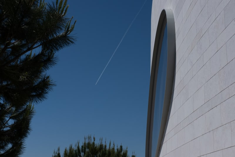A detail shot of one oval window of the Champalimaud Foundation. On the right the window is shown at an acute angle, with deep blue sky behind and tree ferns encroaching. In the background a plane can be seen flying away with a white contrail visible against the deep blue sky.