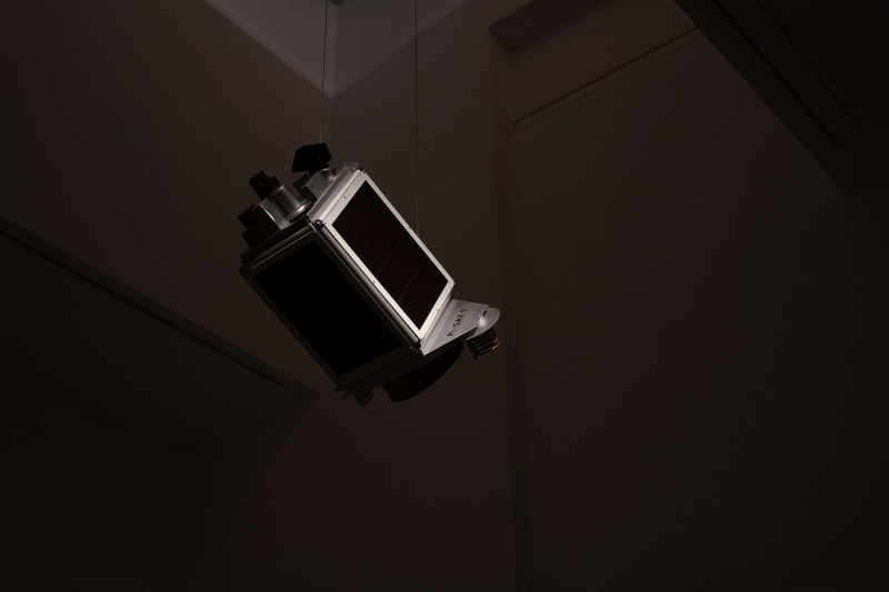 A model of a satellite is just visible in a dark gallery interior.