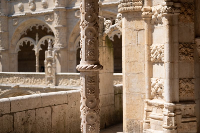 An exterior view of the internal courtyard in the Jerónimos monastery. Several decorative carved pillars in light sandy stone can be seen in strong sunlight.