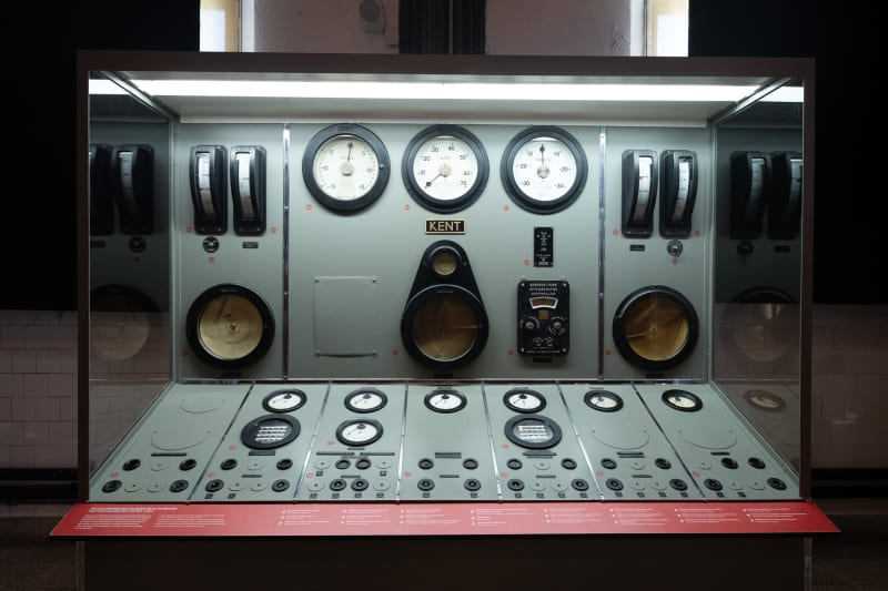 Looking straight on to a large control panel in Maat. The panel has a several columns of controls and dials and has a light grey-green surface colour.